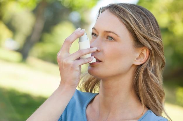 Vrouw die astmainhaleertoestel in park gebruikt