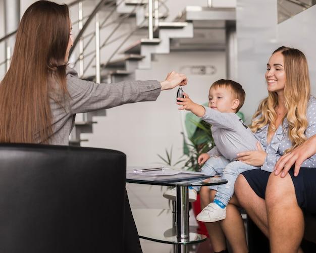 Vrouw die autosleutels geeft aan een baby