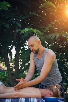 Vrouw die ayurvedische ontspannende massage in kuuroordcentrum krijgen openlucht