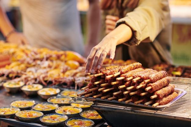 Vrouw die aziatisch straatvoedsel koopt