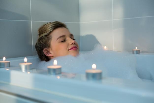 Vrouw die bad in badkuip neemt