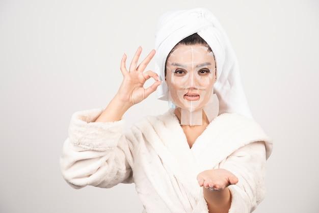 Vrouw die badjas en handdoek met gezichtsmasker draagt.