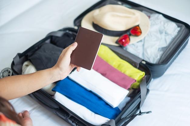 Vrouw die bagage op het bed inpakt en paspoort vasthoudt