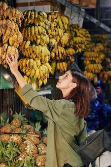 Vrouw die bananen kiest