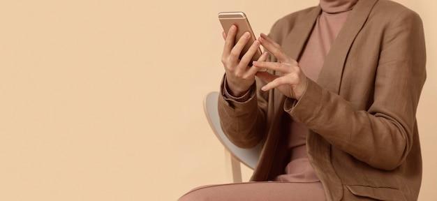 Vrouw die bedrijfskleding draagt die mobiele telefoon met behulp van