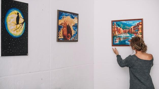Vrouw die beeld op muur plaatst