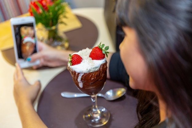 Vrouw die beelden van heerlijke aardbei van ijs witte mengsels met een slimme telefoon neemt.