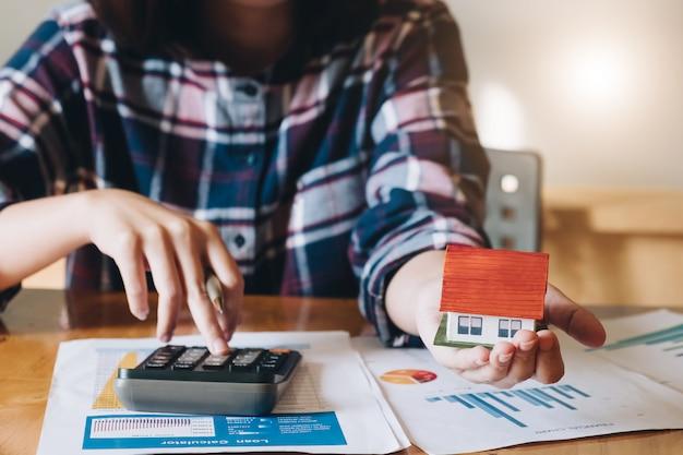 Vrouw die begroting berekent alvorens onroerende goederenprojectcontract te ondertekenen