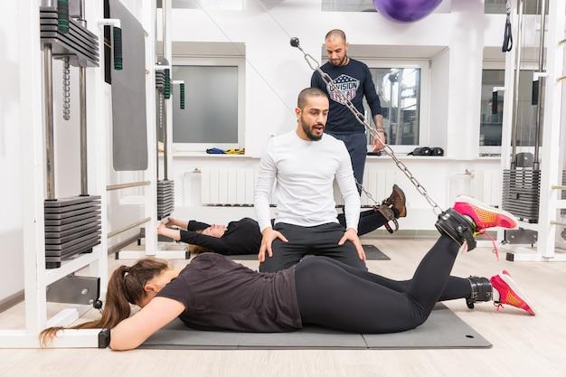 Vrouw die benen met persoonlijke trainer bij gymnastiek uitoefent