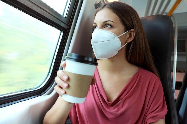 Vrouw die beschermend gezichtsmasker draagt dat koffiekop houdt op openbaar vervoer