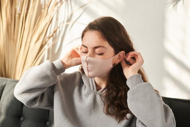 Vrouw die beschermend herbruikbaar masker draagt. vrouw die stoffen masker draagt voor het coronavirus
