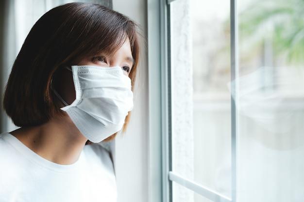 Vrouw die beschermend masker draagt dat door het venster kijkt