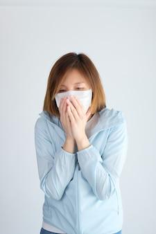 Vrouw die beschermend masker draagt dat handen op haar gezicht zet