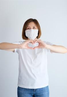 Vrouw die beschermend masker draagt dat hart met handen doet