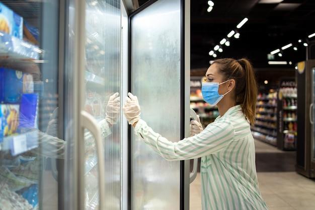 Vrouw die beschermend masker en handschoenen draagt die boodschappen en voedsel koopt tijdens wereldwijde coronaviruspandemie
