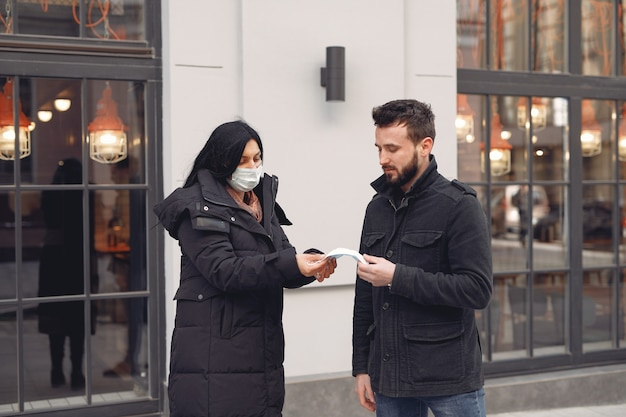 Vrouw die beschermend masker geeft aan een man
