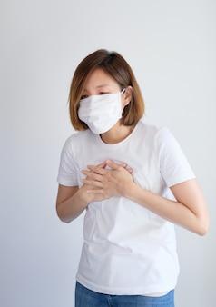 Vrouw die beschermend masker met haar handen op haar borst draagt