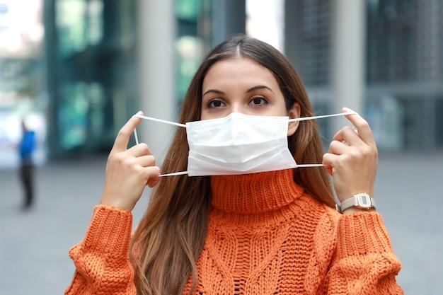 Vrouw die beschermend masker op gezicht in stadsstraat draagt