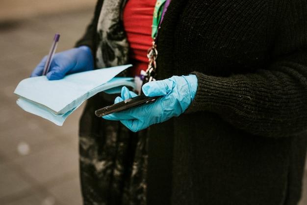 Vrouw die beschermende latexhandschoenen draagt en een telefoon houdt.