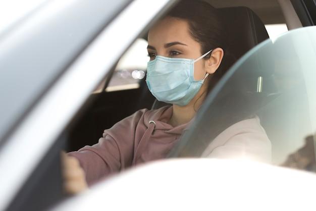 Vrouw die beschermingsmasker in auto draagt