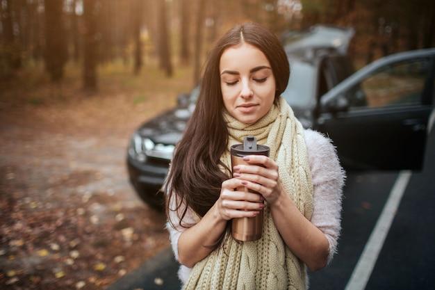 Vrouw die beschikbare kop van koffie naast auto houdt. close-up van de hand. herfst concept. herfst bos reis met de auto