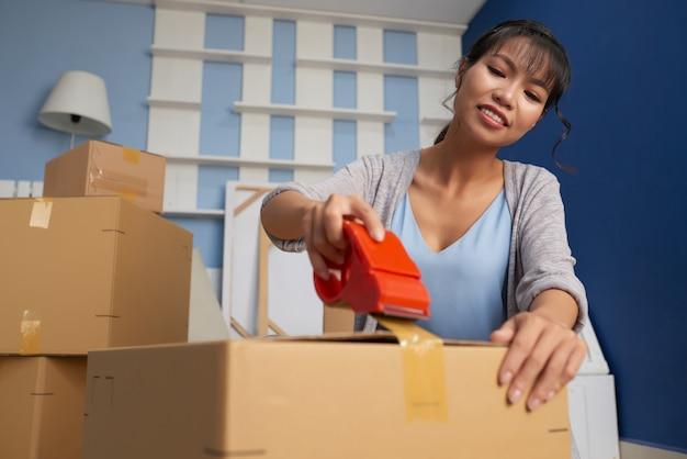 Vrouw die bewegende doos verzegelt