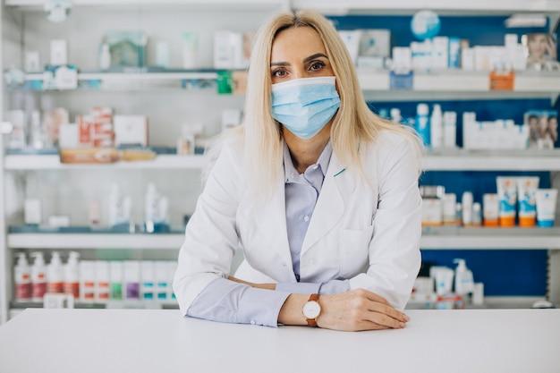 Vrouw die bij apotheek werkt en jas draagt