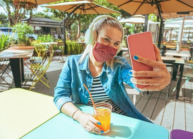 Vrouw die bij bar een selfie met gezichtsmasker neemt