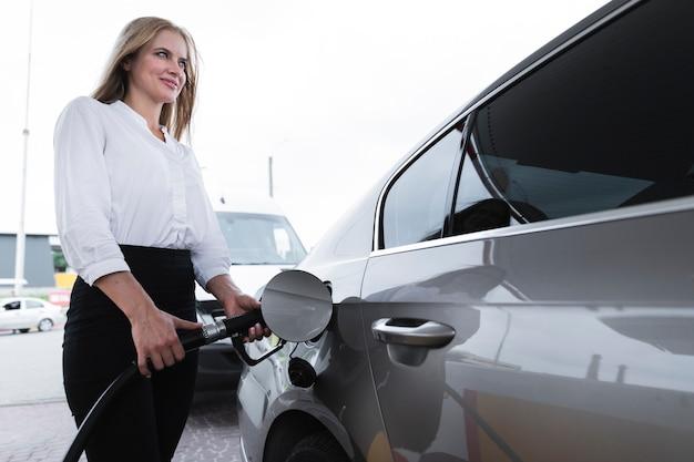 Vrouw die bij benzinestation van brandstof voorziet