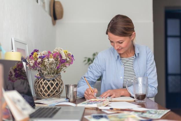 Vrouw die bij bureau in notitieboekje schrijft