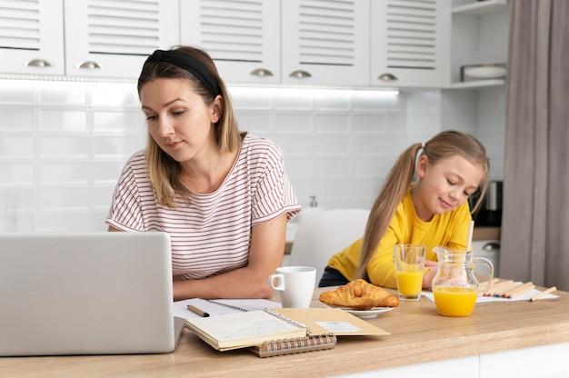 Vrouw die bij bureau met meisje werkt