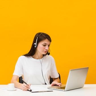 Vrouw die bij bureau werkt terwijl het dragen van hoofdtelefoon en het bekijken laptop