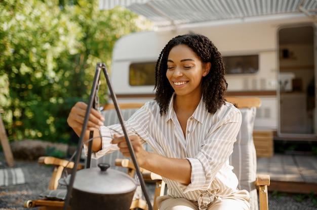 Vrouw die bij de camper kookt, kampeert in een aanhangwagen. stel reist op busje, vakanties op camper