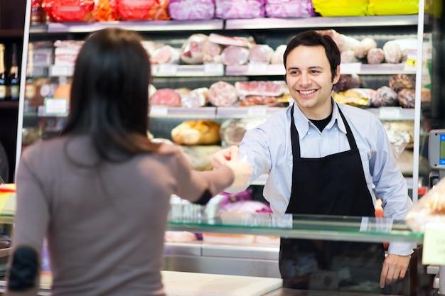 Vrouw die bij de kruidenierswinkelopslag winkelt