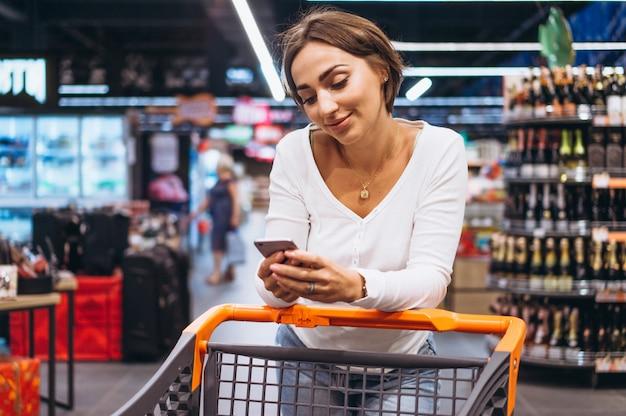 Vrouw die bij de supermarkt winkelt en op telefoon spreekt