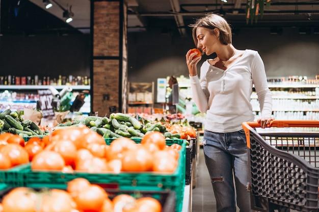 Vrouw die bij de supermarkt winkelt
