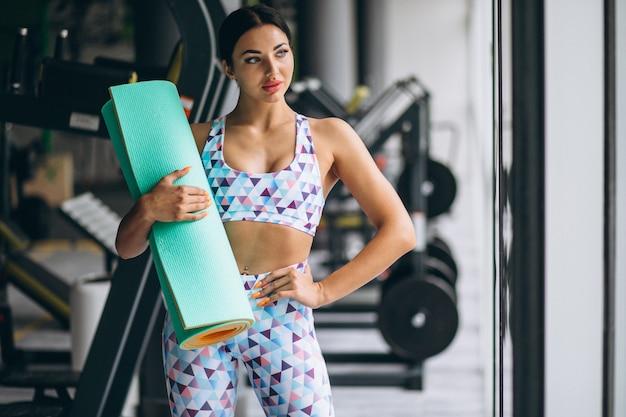 Vrouw die bij de yogamat van de gymnastiekholding uitoefent