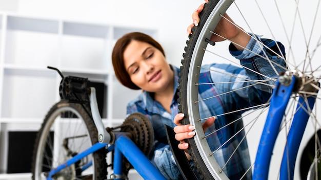 Vrouw die bij fiets werkt