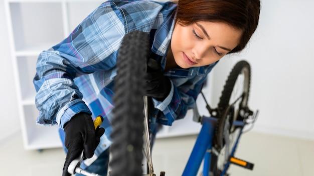 Vrouw die bij fietswiel werkt
