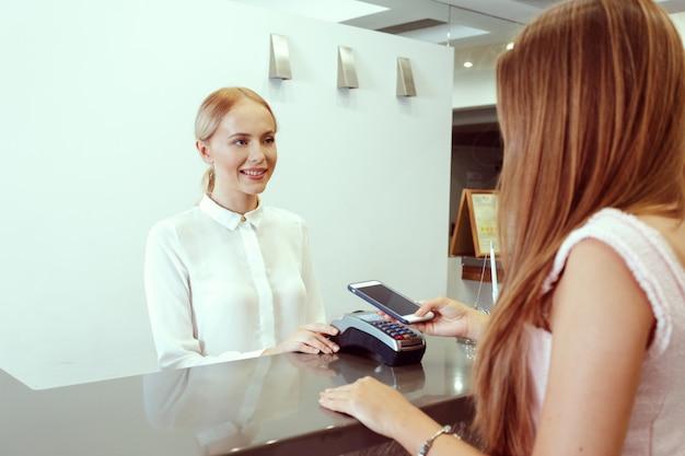 Vrouw die bij hotelontvangst controleert