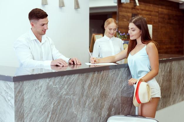 Vrouw die bij hotelontvangst inchecken