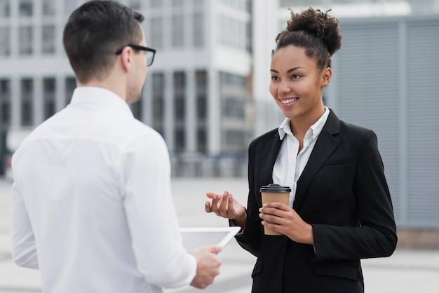 Vrouw die bij medewerker middelgroot schot glimlacht