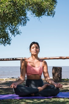 Vrouw die bij strand mediteren