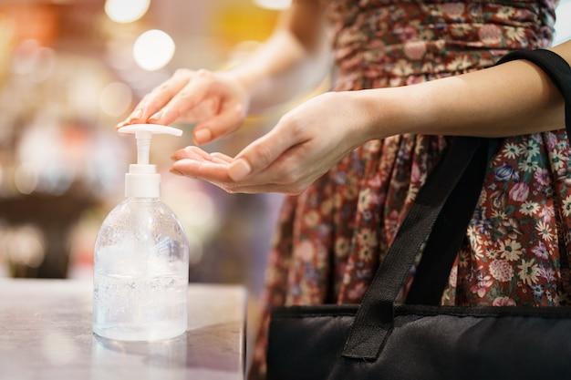 Vrouw die bij supermarkt winkelt voor het opstoken in quarantaine tijdens de epidemie covid-19. haar handen schoonmaken met ontsmettingsgel.