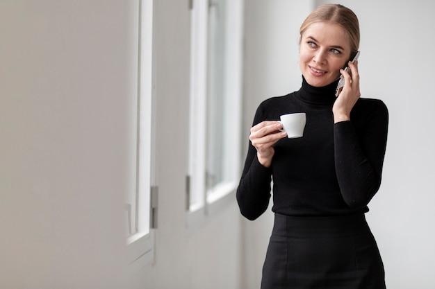 Vrouw die bij telefoon spreekt en kop van koffie houdt
