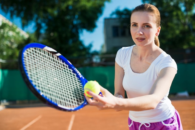 Vrouw die bij tennis voorbereidingen treft te dienen