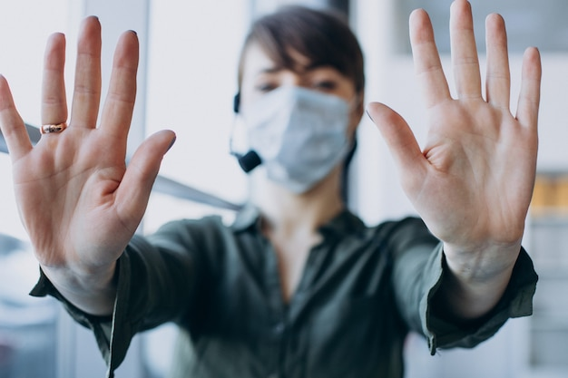 Vrouw die bij verslagstudio werkt en masker draagt