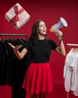 Vrouw die bij winkelen in een megafoon schreeuwt terwijl het vangen van een gift