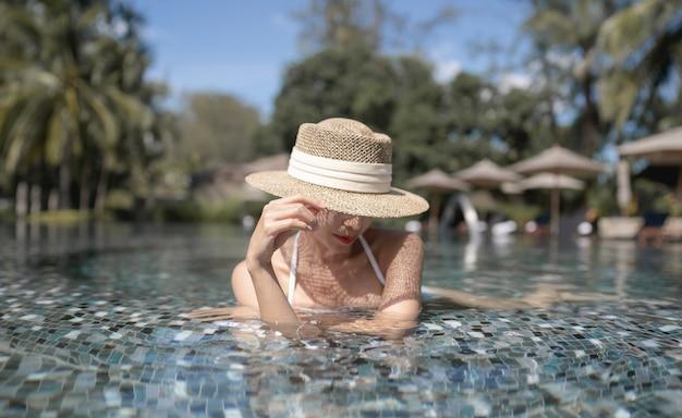 Vrouw die bikini en strohoed draagt die betrekking hebben op gezicht ontspannen in het zwembad. spa-behandelingen concept.