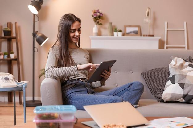 Vrouw die binnen aan digitale tablet werkt